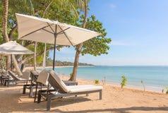 海滩懒人和遮阳伞,巴厘岛 免版税库存照片