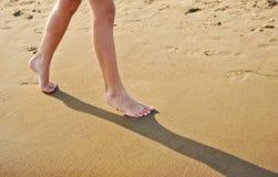 海滩旅行-走在沙子海滩的女孩把脚印留在沙子 女性脚和金黄沙子特写镜头细节  免版税库存照片