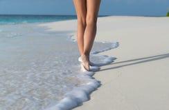 海滩旅行-走在沙子海滩的妇女把脚印留在沙子 库存照片