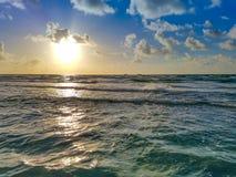 海滩日出、海浪、云彩和蓝天 免版税库存照片