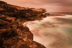海洋日出风景有波状云和岩石的 免版税库存照片