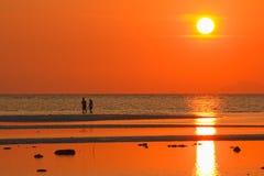 海滩日落的恋人与金黄光线影响 库存照片