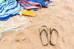 海滩沙子毛巾人拖鞋黑色黄色 免版税图库摄影