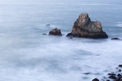 海洋沿海岩石与被弄脏的波浪的晚上 库存照片