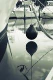 海洋浮体垂悬水面上在被停泊的小船之间在Tutukaka 免版税库存图片