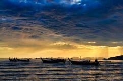 与渔船的海洋海岸多云五颜六色的日落 免版税库存照片