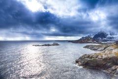海滨海岸线的分开的议院在反对山的挪威 免版税库存照片
