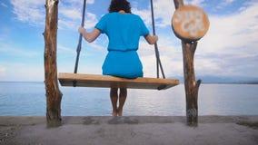 海洋海滩在巴厘岛 女孩 摇摆 绿松石海洋,清楚的天空 一件蓝色礼服的女孩在摇摆 从这个地点 影视素材