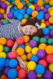 海绵球水池的逗人喜爱的微笑的女孩 免版税图库摄影