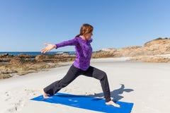 海滩瑜伽实践 免版税库存图片
