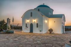 海滩的一个小白色教会在帕福斯,在黎明期间的塞浦路斯 太阳在天际上升起并且照亮教会 免版税库存图片