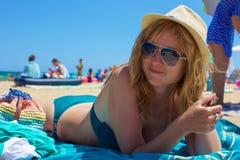海滩的一个微笑的金发碧眼的女人 库存照片