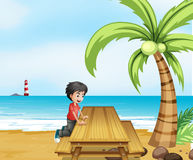 海滩的一个男孩与在椰子树附近的一张木桌 免版税库存照片