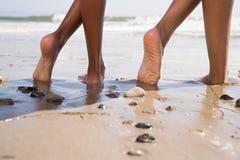 海滩的两个人与盘的腿 免版税库存照片