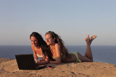 海滩的两个女孩使用个人计算机 免版税库存照片