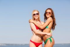 海滩的两个微笑的少妇 免版税图库摄影