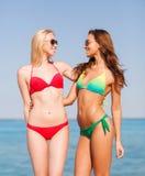 海滩的两个微笑的少妇 免版税库存图片