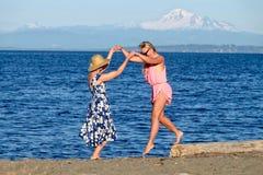 海滩的两名妇女由获得蓝色的海洋乐趣 免版税图库摄影