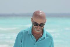 海滩的中年人在绿松石衬衣 免版税库存照片