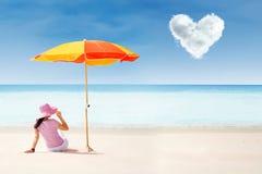 海滩的亚裔游人在伞下和爱覆盖 免版税库存照片