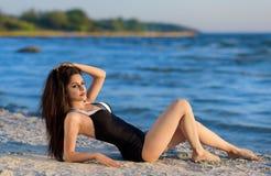 海滩的亭亭玉立的深色的妇女 免版税库存图片