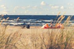 海滩的人在有风筝的海附近 免版税库存照片