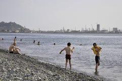 海滩的人们巴统在背景巴统港口 库存照片