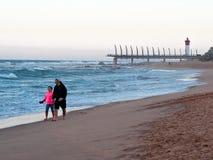 海滩的人们在Umhlanga岩石,与千年码头和灯塔在背景中 库存照片