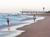 海滩的人们在Umhlanga岩石,与千年码头和灯塔在背景中 库存图片