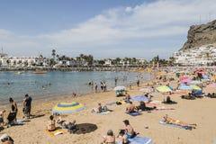 海滩的假日游客在Puero在大加那利岛的de Mogan 图库摄影