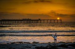 海滩的冲浪者在日落在圣地亚哥加利福尼亚 免版税库存照片