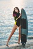 海滩的冲浪者女孩在日落 库存图片