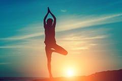 海洋的凝思妇女在惊人的日落期间 瑜伽剪影 图库摄影