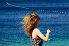 海滩的卷曲白肤金发的妇女 免版税图库摄影