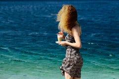 海滩的卷曲白肤金发的妇女 库存照片