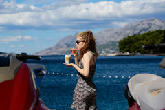 海滩的卷曲白肤金发的妇女 免版税库存图片