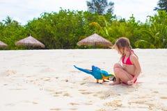 海滩的可爱的小女孩与五颜六色的鹦鹉 免版税图库摄影