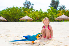 海滩的可爱的小女孩与五颜六色的鹦鹉 库存图片