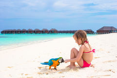 海滩的可爱的小女孩与五颜六色的鹦鹉 免版税库存照片