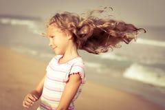 海滩的可爱的愉快的微笑的女孩 免版税库存图片