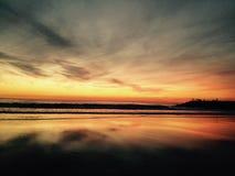 从海滩的壮丽落日视图与后面的渔夫 库存照片