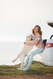 海滩的女孩与一辆白色拉布拉多和白色汽车 免版税库存图片
