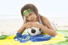 海滩的女孩与巴西旗子和橄榄球 免版税库存照片