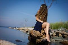 海滩的女孩在日志 免版税库存图片