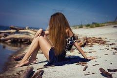 海滩的女孩在日志 免版税库存照片