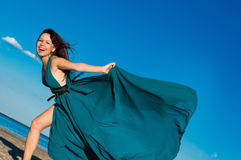 海滩的女孩在美丽的长的礼服 免版税图库摄影