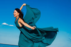 海滩的女孩在美丽的长的礼服 免版税库存图片