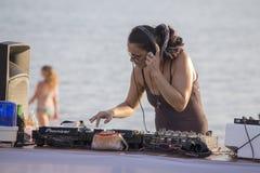 海滩的女孩DJ棍打演奏在海岛酸值Phangan,泰国的混合的音乐 库存照片