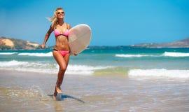 海滩的妇女与冲浪板 免版税图库摄影
