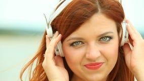 海滩的妇女听到音乐的 图库摄影